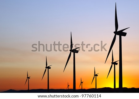 Wind power at sunset - stock photo