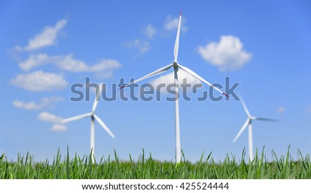 Wind power energy. Green field and wind turbines generating electricity. - stock photo