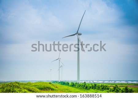 wind power farm in cloudy, renewable electric energy production at chinese coastal. - stock photo