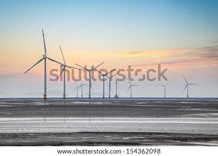wind power farm on the coastal mud flat in sunrise - stock photo