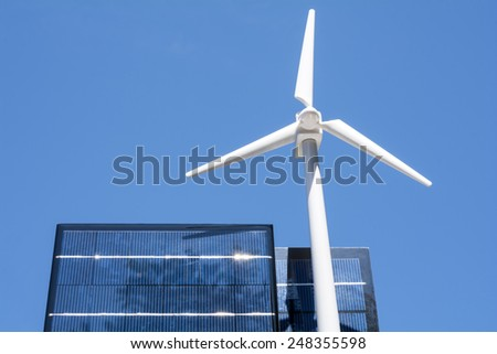 Wind power generator model and solar panel under blue sky