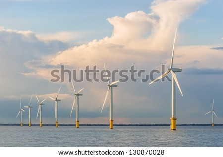 wind power generators farm at sea with stormy clouds