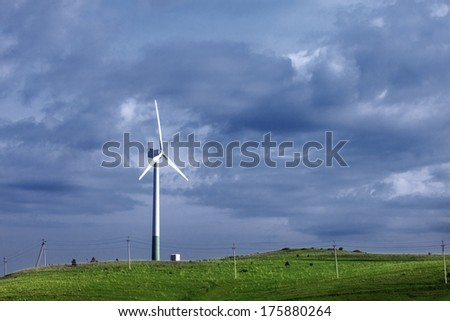 Wind Power in the field under clouds - stock photo