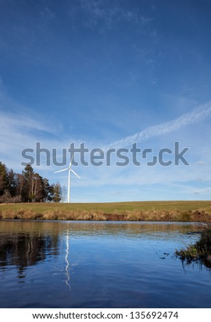 wind power mills with reflection in water - stock photo