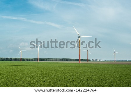 Wind power plant in the wheat fields at dusk in Netherlands