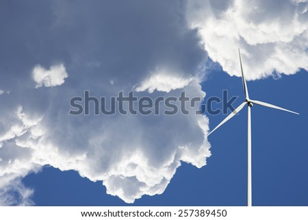 wind power plant set against a clear sky and puffy clouds - stock photo