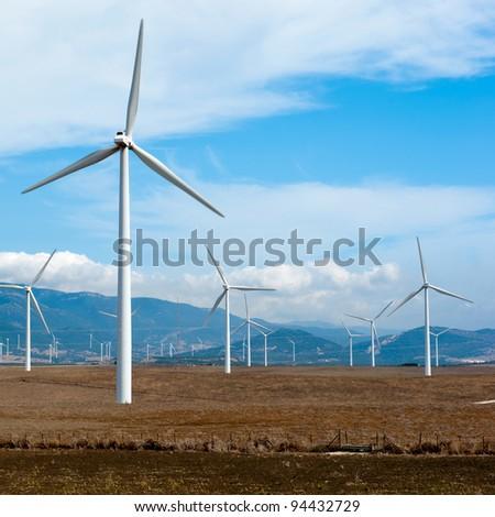 Wind power station - wind turbine against the blue sky - stock photo