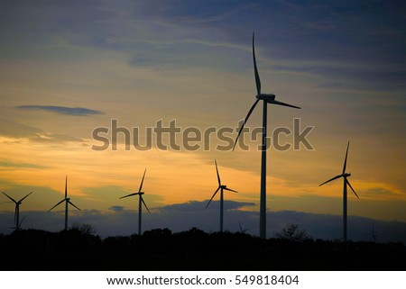 Wind power stations silhouetted against the sunset