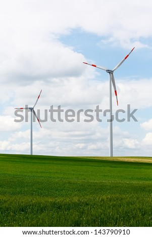 Wind power turbine spins over green landscape