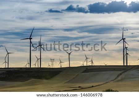 Wind power turbines at sunset - stock photo
