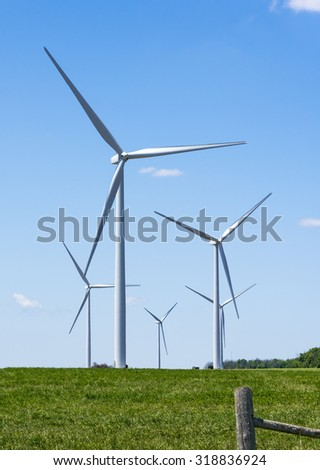 Wind power turbines in a farmers field on a blue sky day in Ontario Canada.