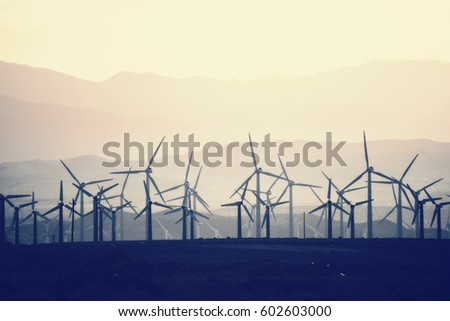 Wind power turbines in the landscape A large number of turbine powers on a plain against a mountain backdrop