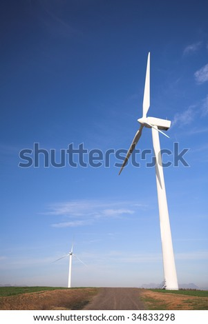Wind powered electricity generators standing against the blue sky in a green field on the wind farm - stock photo