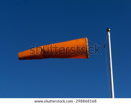 Wind Sock; Orange wind-sock flying from white post, against deep blue sky; good and easily-extendable copy-space  - stock photo