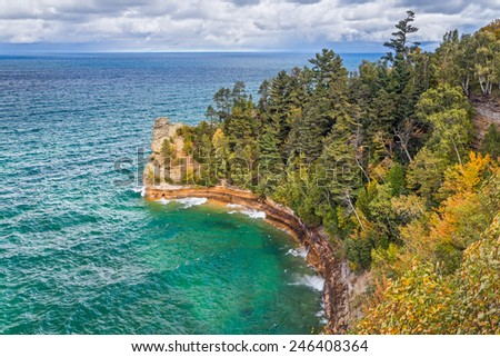 Wind swept waves crash at the base of Miner's Castle, a rock formation jutting into Lake Superior at Upper Peninsula Michigan's Pictured Rocks National Lakeshore. - stock photo