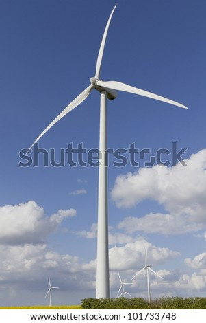 Wind turbine against a blue sky with white fluffy clouds