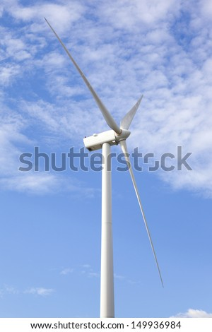 Wind turbine against cloudy blue sky - stock photo
