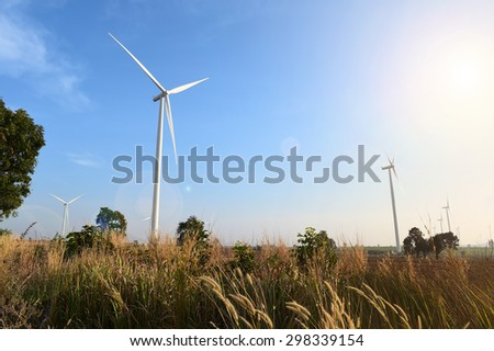 wind turbine against cloudy blue sky background.