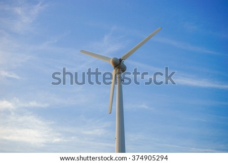 wind turbine against partly cloudy blue sky - stock photo
