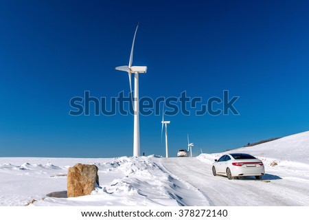 Wind turbine and Car with blue sky in winter landscape. - stock photo