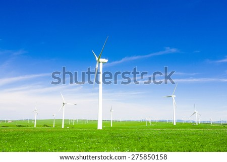 wind turbine and meadow under blue sky