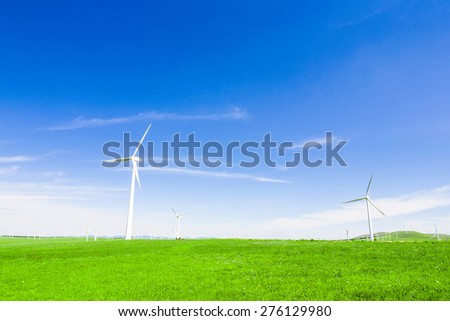 wind turbine and meadow under sky - stock photo