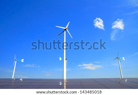 Wind turbine and  solar energy panels with blue sky.