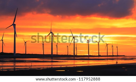 wind turbine array silhouettes at sea shore - stock photo