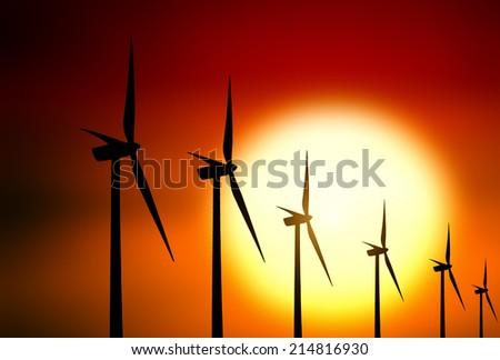 Wind turbine at sunset background - stock photo