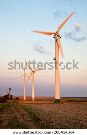 Wind turbine at sunset on green field. - stock photo
