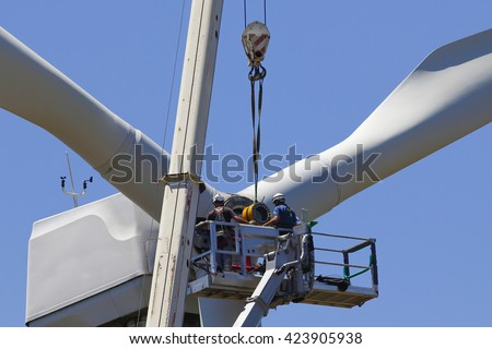 Wind turbine being repaired, assisted by crane and elevator - stock photo