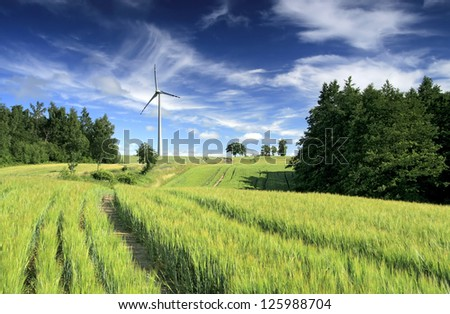 Wind turbine between fields - stock photo