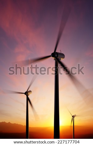 Wind Turbine blades spinning at close range with golden sunset. Focused on tip of front blade