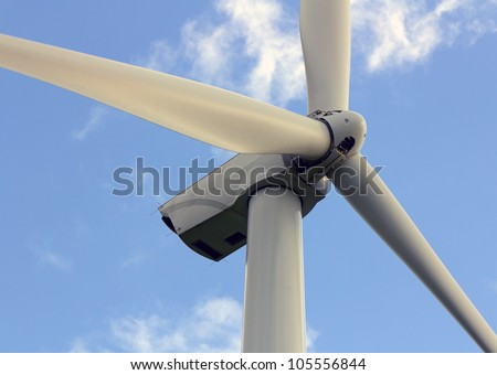 Wind turbine closeup on the blue sky - stock photo