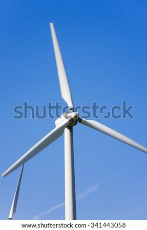 Wind turbine electricity generator against blue sky. UK - stock photo