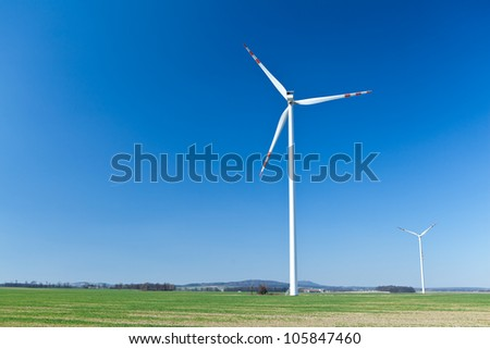 Wind turbine farm, alternative energy on green field, ecology and business in summer nature.