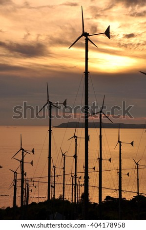 Wind turbine farm and sunset  - stock photo