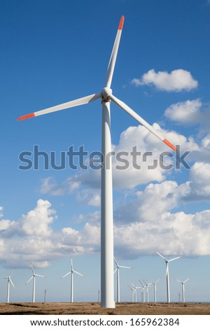 Wind turbine farm over the blue clouded sky - stock photo