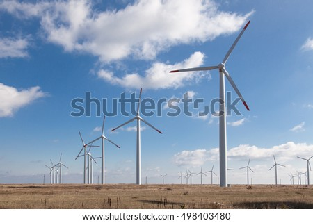 Wind turbine farm over the blue clouded sky