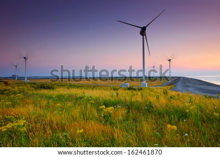 Wind turbine farm with purple sky and grass in front - stock photo