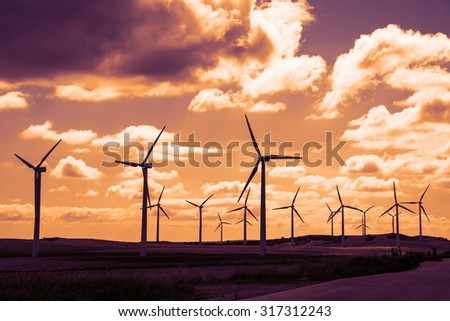 Wind turbine field at sunset, dramatic sky