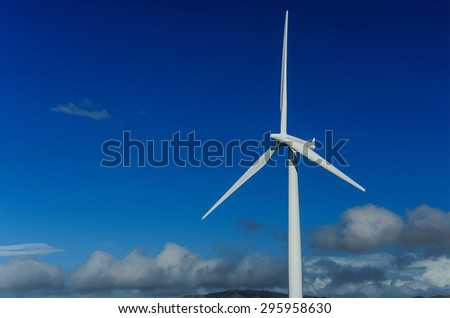 Wind turbine generating electricity on blue sky. Ecology - stock photo