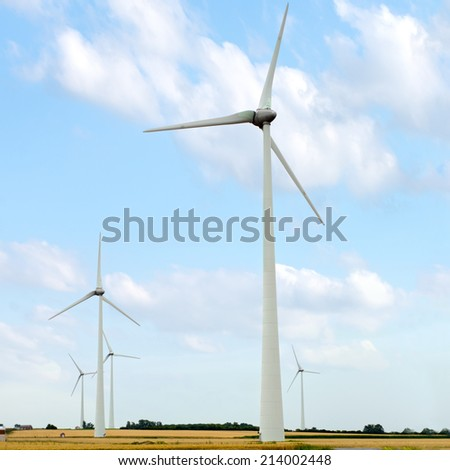 Wind turbine generators in a field against blue sky - stock photo