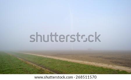Wind turbine in a foggy field in spring - stock photo
