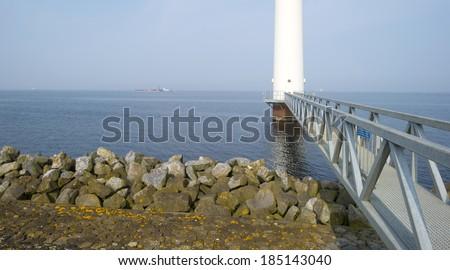 Wind turbine in a lake along a dike - stock photo