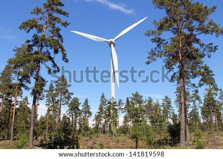 Wind turbine in pine forest near Hanko, Finland, on a bright day at summer. - stock photo