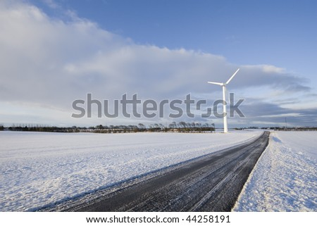 Wind turbine in snow filled landscape with a small country road running through