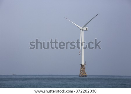 Wind turbine in the ocean using wind power to create green energy for a healthy environment.  - stock photo