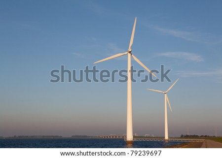 Wind turbine in the water producing alternative energy during sunset
