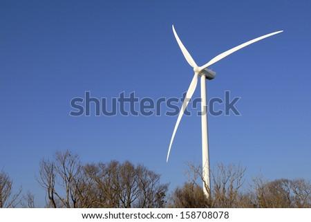 Wind Turbine in winter trees. - stock photo